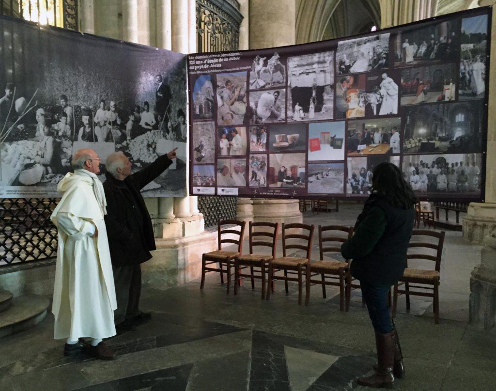 Fr. Christian Eeckhout devant une bannière présentant l'École Biblique.